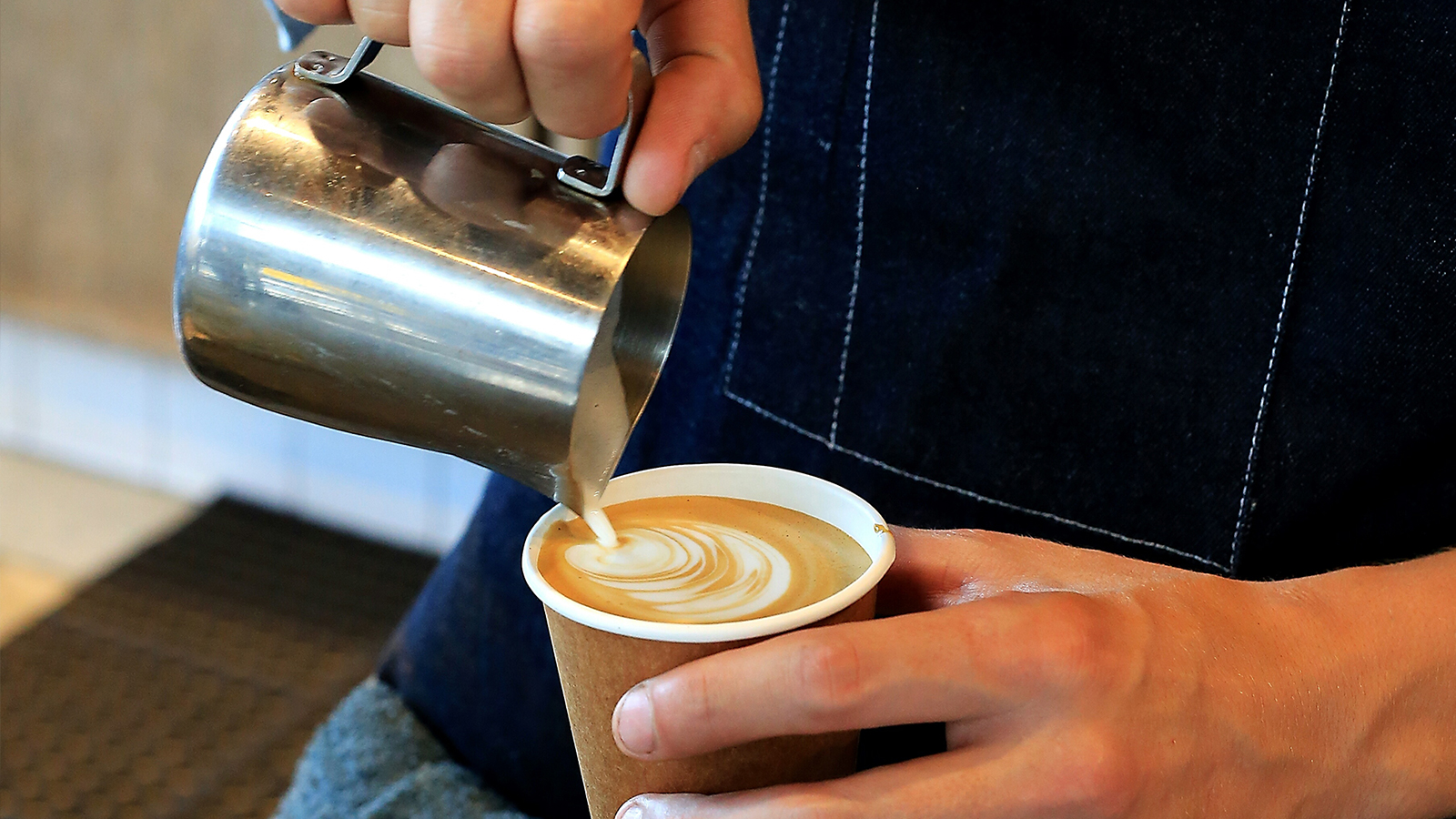 Barista adding steamed milk to expresso making a Cappuccino.