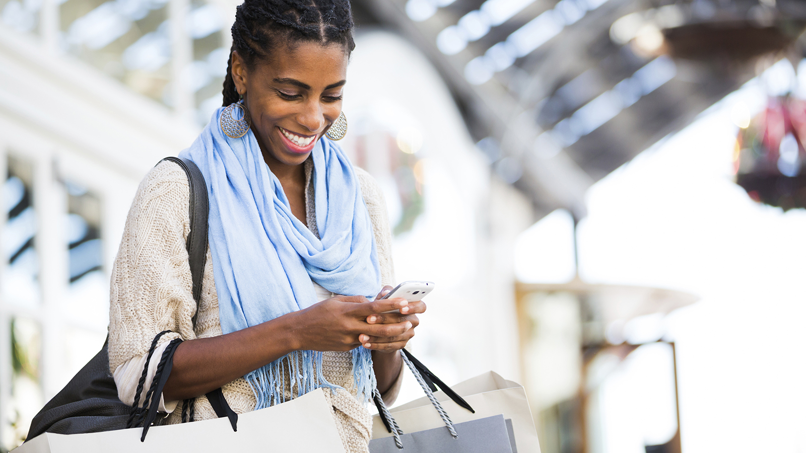 Woman holding shopping bags and checking out online deals on her mobile phone.