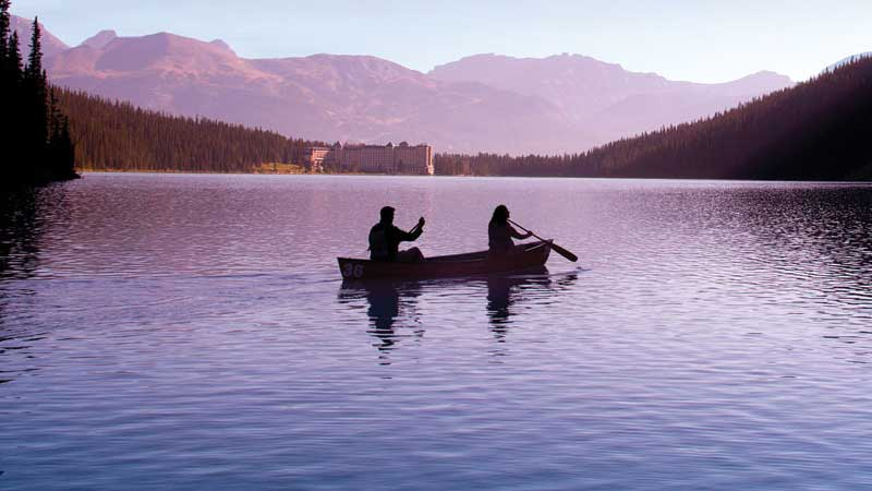 Two people in a boat paddling in a fjord during sunset with mountains, trees, and a castle in the distance.