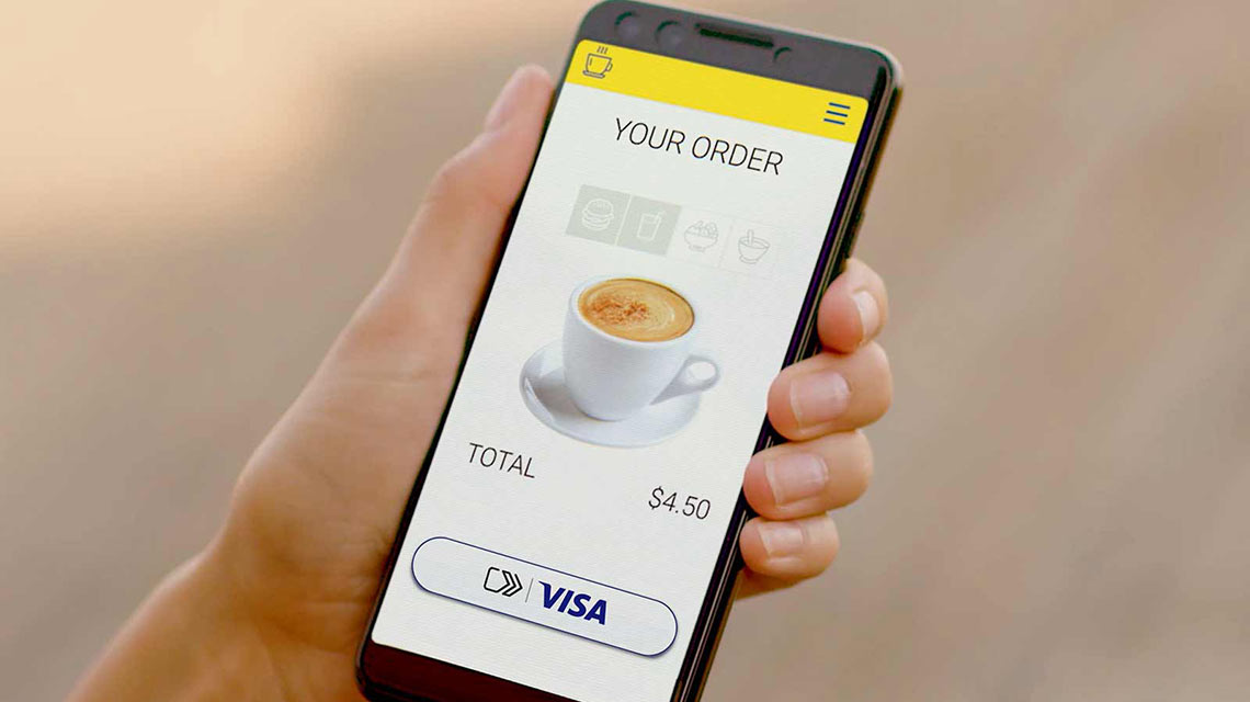 Person holding cellphone and ordering a cup of coffee using Visa Checkout service.